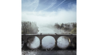 Cyclist crossing the Dordogne river, Limeuil, France.