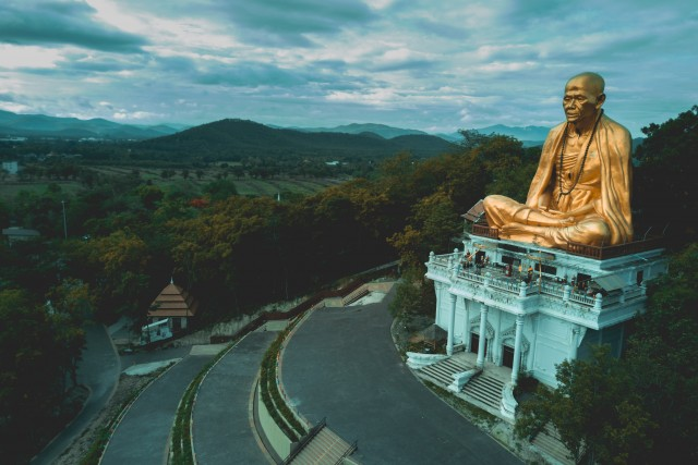 Golden Monk Statue Looks Over Town In Thailand