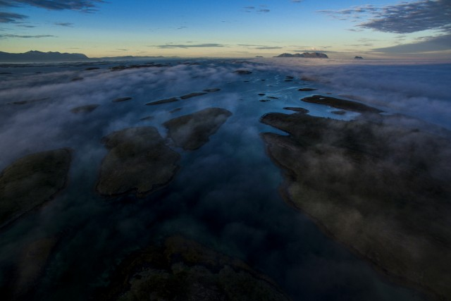 Aerial view of islands covered by morning mist, with small fishing village, Norway