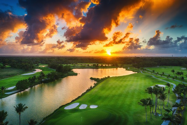 Aerial view of tropical golf course at sunset.