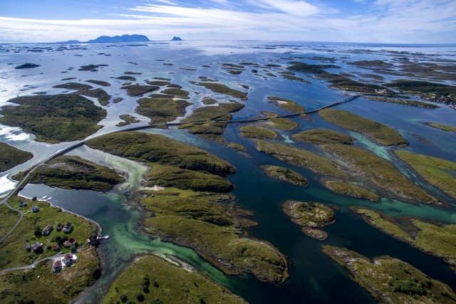 A small fishing village is located far away from the mainland of Norway,  lots of islands connected by roads and bridges.