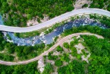 Aerial view of drone over mountain road and curves going through forest landscape