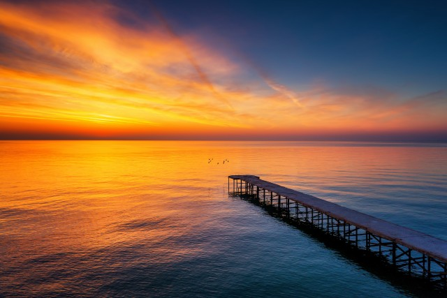 Sunrise over the old broken bridge in the sea