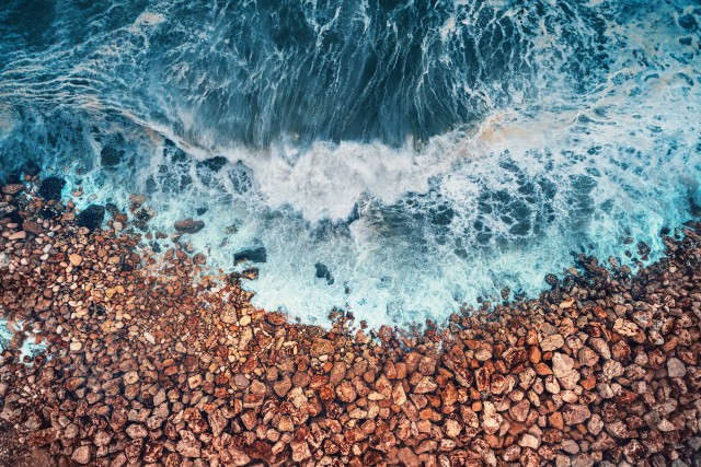 Aerial view of sea waves and rocky coast.
