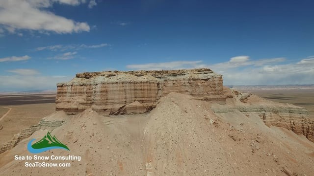 Aerial drone footage of butte and monument in Utah desert landscape
