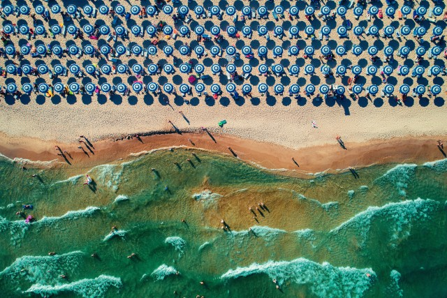 Aerial drone view of a beautiful beach with white sand and umbrellas.