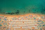 Aerial top view on the beach. People, umbrellas, sand and sea waves