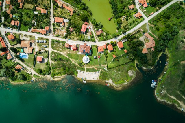 Aerial view of small village on a lake coast with calm clear water.