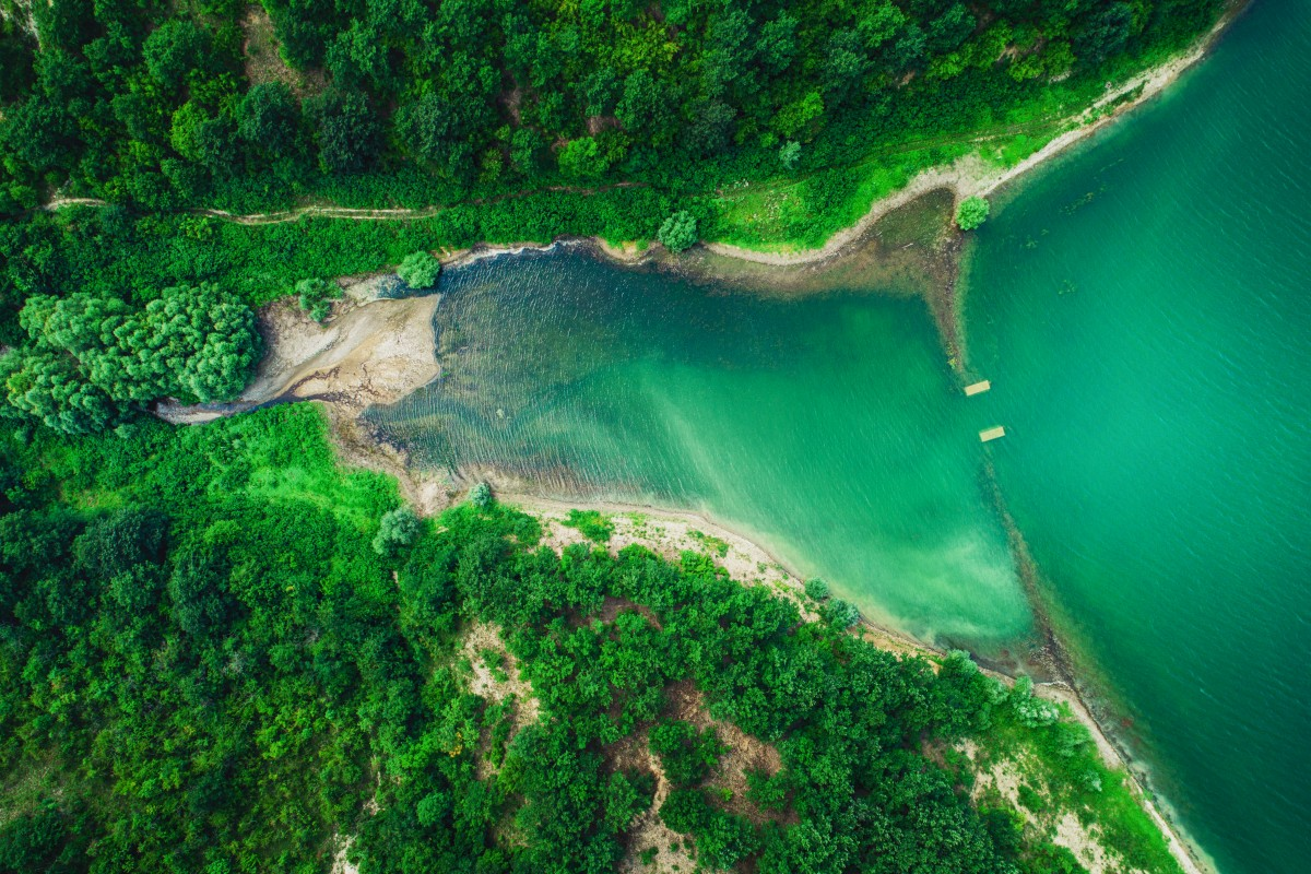 Aerial top view of lake between mountain forest, beautiful panorama.