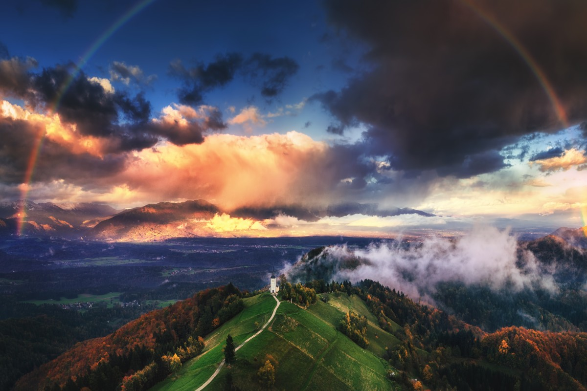 Jamnik, Slovenia – Aerial view of rainbow over the church of St. Primoz in Slovenia near Jamnik with beautiful clouds and Julian Alps at background.