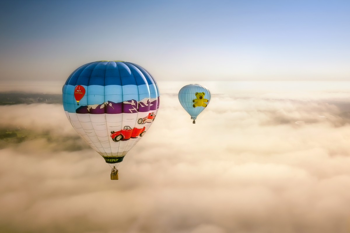 Two Hot Air Balloons in Flight over Fog