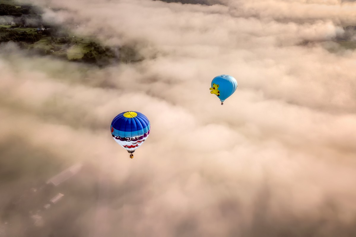 Top View of Two Hot Air Balloons in Flight over Cloud