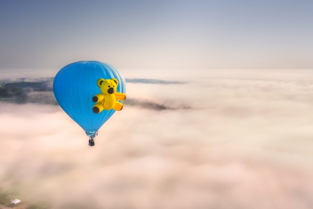 Blue Hot Air Balloon with Teddy in Flight over Fog