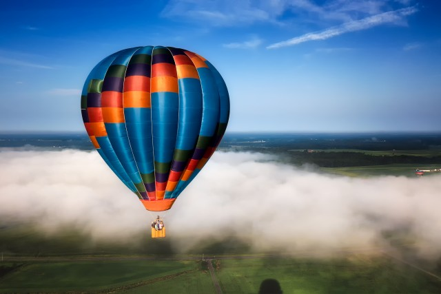 Colorful Hot Air Balloon in Flight on a Foggy Morning