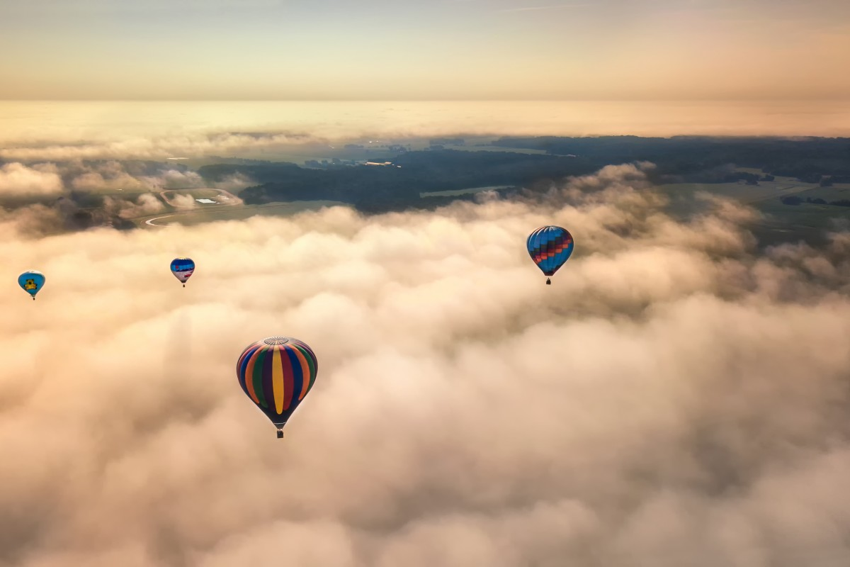 Four Hot Air Balloons in Flight Over Fog