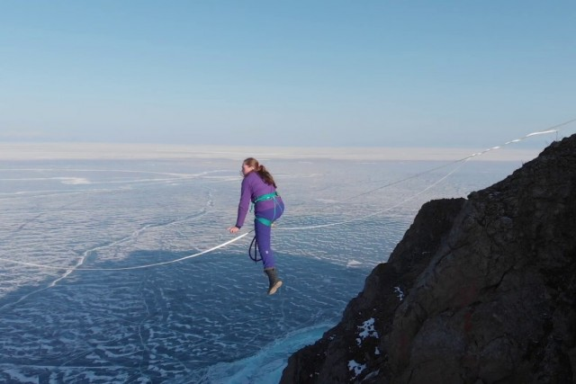 a brave girl walks a tightrope over an abyss.