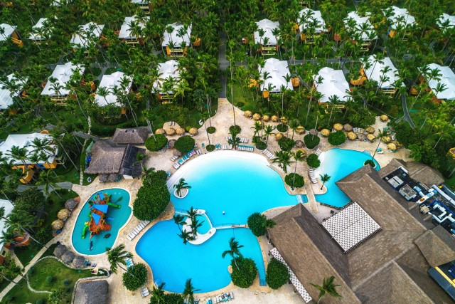 Aerial view of tropical swimming pool and palm trees in luxury resort.
