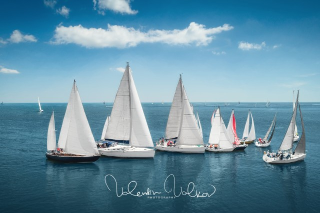 Regatta sailing ship yachts with white sails at opened sea