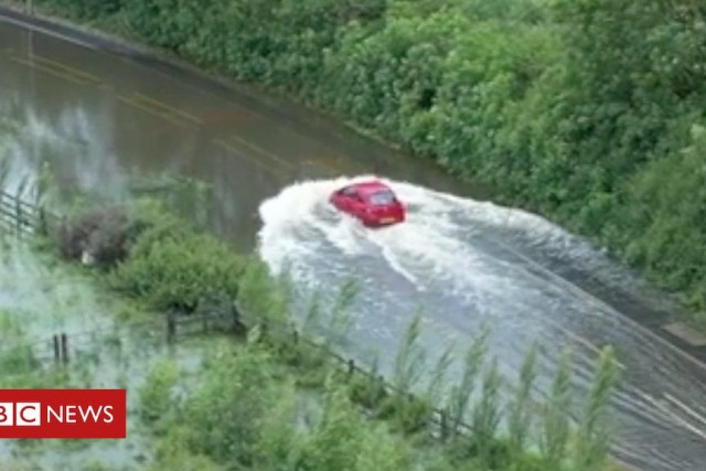 Drone footage captures driver stuck in flood water – BBC News