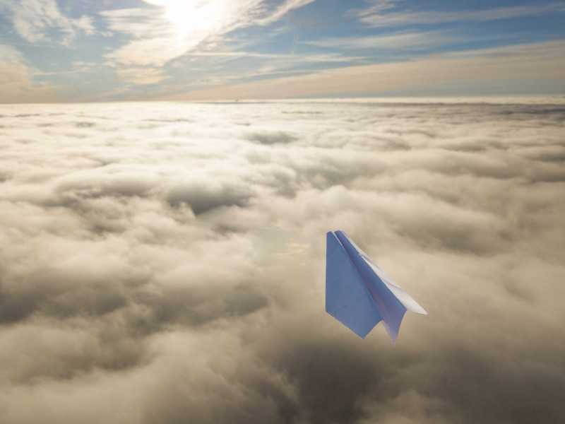 Paper plane above clouds